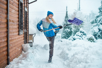 A woman cleans the snow in her yard in a country house.