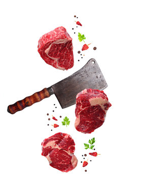 Raw marbled ribeye steak and butchers knife isolated