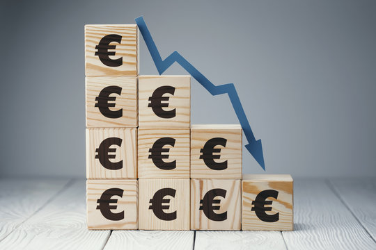 Falling graph on wooden cubes with euro signs, on neutral background