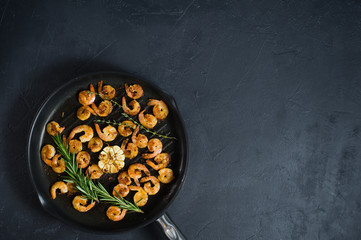 Pan with fried shrimps, fried garlic, rosemary. The view from the top. Black background. Space for text.