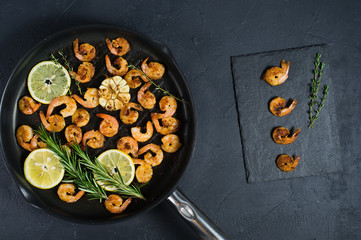 Pan with fried shrimps, fried garlic, rosemary. A stone plaque with shrimp sauce. The view from the top. Black background.