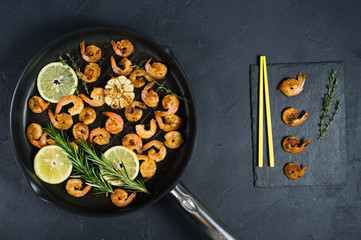 Pan with fried shrimps, fried garlic, rosemary. A stone plaque with shrimp sauce. Yellow Japanese chopsticks. Top view. Black background.