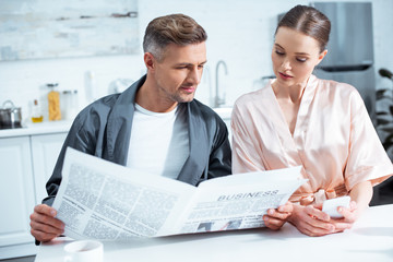 selective focus of couple in robes reading business newspaper in kitchen
