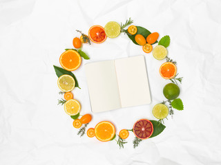 many different fresh citrus fruits on white crumpled paper background
