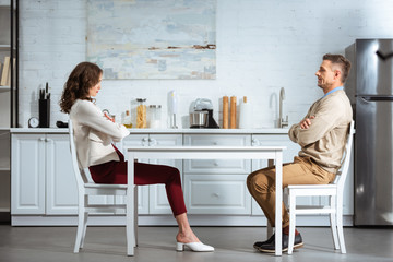 dissatisfied couple looking at each other while sitting with arms crossed at table in kitchen Wall mural