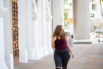 Pretty young woman walking on the city street. Casual fashion, plus size model. xxl women on nature.