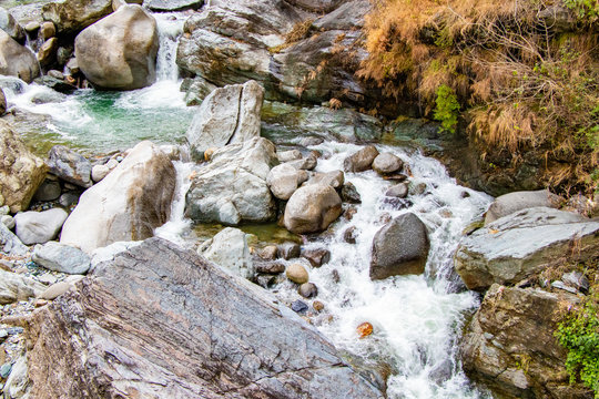 Flowing stream through green mossy rocks  in forest, moss on rocks forest river flowing through  the rapids