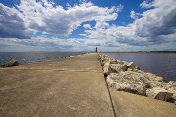 Manistique Michigan Lighthouse. Long pier with diminishing perspective under a sunny blue sky with lighthouse at the horizon.