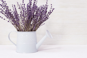 Lavender flowers in watering can, old wooden background, copy space