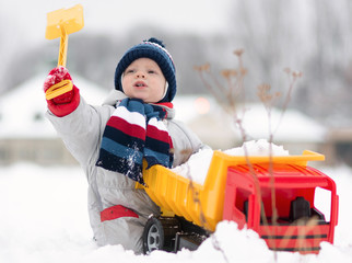 little baby boy playing with his favourite toy at the snowtime