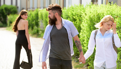 Womaniser. Unfaithful love. Love triangle and threesome. Man cheating his wife or girlfriend. Bearded man looking at other girl. Hipster choosing between two women. Betrayal and infidelity