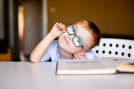 Cute toddler boy with down syndrome with big glasses reading intesting book