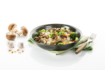 Veganes Gericht: Naturreis mit Pilzen, Erbsen, Brokkoli, Freisteller
