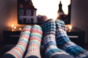 Cozy woolen socks. Couple watching tv in winter. Man and woman using online streaming service for movies and series. Relaxing quality time on sofa couch. People in warm home living room enjoying life.