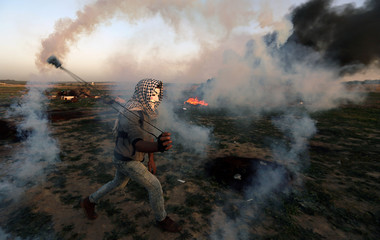 Palestinian demonstrator uses a sling to hurl back a tear gas canister fired by Israeli troops during a protest at the Israel-Gaza border fence, in the central Gaza Strip