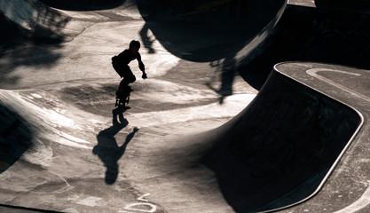 Skater als silhouette im Gegenlicht, im Hintergrund Skatepark