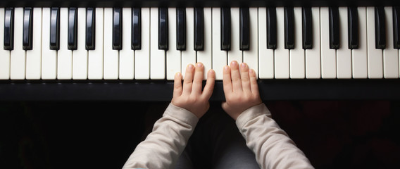 Children's hands learn to play the piano