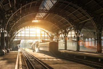Old railway station with a train and a locomotive on the platform awaiting departure. Evening sunshine rays in smoke arches. Fotomurales