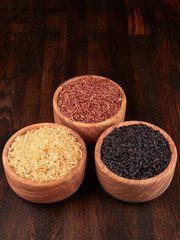 Uncooked black, red and integral rice in olive wood bowls, on a dark rustic wooden board.