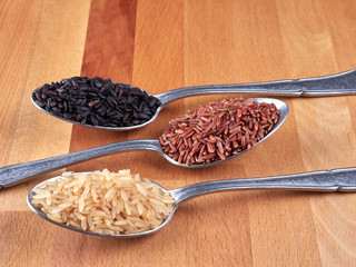 Uncooked black, red and integral rice on silver spoons, on a rustic wooden board