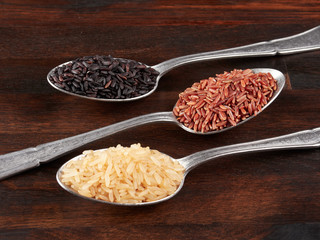 Uncooked black, red and integral rice in olive wood bowls, on a rustic wooden board.