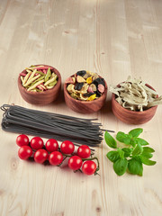Dried pasta: colorful orechiette, fusilli , tagliatelle, spaghetti, fresh tomatoes and basil, on a wooden board