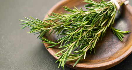 Fresh rosemary bunch on wooden plate