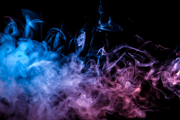 Thin smoothly curling streams of colored smoke evaporate against a black background illuminated with blue and pink light like tongues of fire.