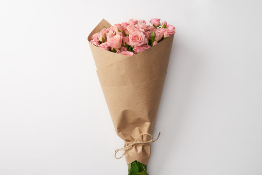 bouquet of beautiful pink roses wrapped in craft paper on grey