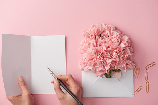 cropped shot of woman writing on greeting card and pink flowers in envelope isolated on pink