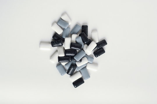 black, grey and white chewing gum on white background