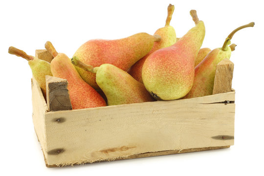 """fresh and colorful """"Carmen"""" pears in a wooden crate on a white background"""