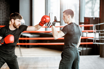 Athletic man fighting during the training with boxing trainer on the boxing ring at the gym