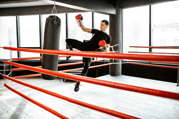 Athletic man kicking punching bag with leg, training kickboxing on the boxing ring at the gym