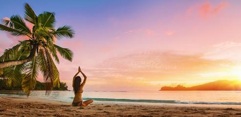 Yoga Concept. Woman Practicing Lotus Pose on Beach