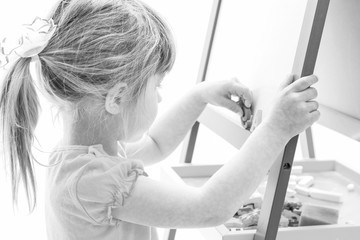 Happy baby girl beautiful painting on the easel on a white background