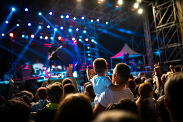 Concert seen from the crowds with a young boy and his father watching the performance
