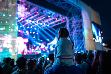 Young girl watching a concert from her dad shoulders