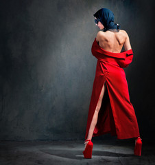 Fashion photo of beautiful woman with naked back in headscarf, red coat and shoes