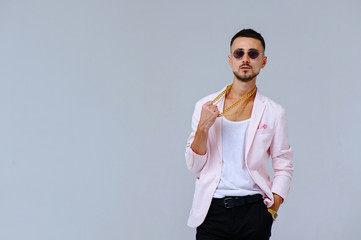 fashionable sophisticated man in a pink jacket and black trousers, wears a gold chain, the expression of emotions gestures with his hands