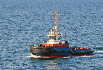 A tugboat with a Danish flag navigates on the sea - Buy this