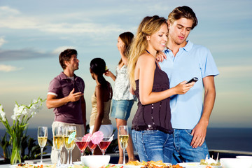 Young couple at outdoor drinks party looking at mobile phone