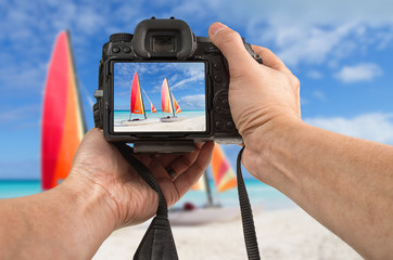 Travel phototography concept. Man's hands holding a DSLR camera taking picture of two catamarans