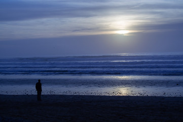 Sunset over main beach in Agadir Morocco showing silhouettes and reflections