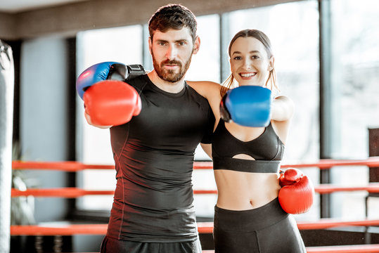 Portrait of an athletic couple in sportswear with boxing gloves hugging together on the boxing ring at the gym