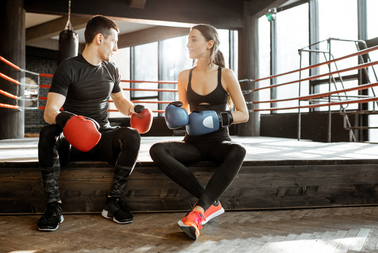 Man and woman in sportswear talking together during the break after the training on the boxing ring