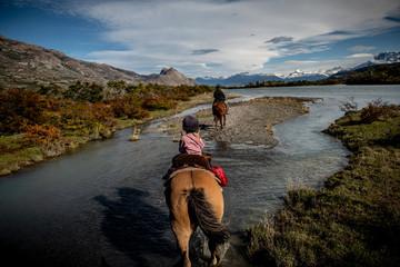 Girl riding horses through river in Mountains