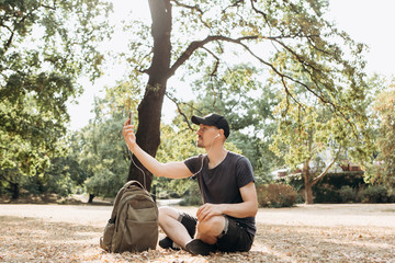 A young guy or student talking on a cell phone via video connection or listening to music or watching a video in an autumn park.