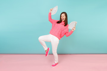 Full length portrait excited woman in knitted rose sweater, white pants holding lots dollars banknotes isolated on bright pink blue pastel wall background in studio. Money concept. Mock up copy space.
