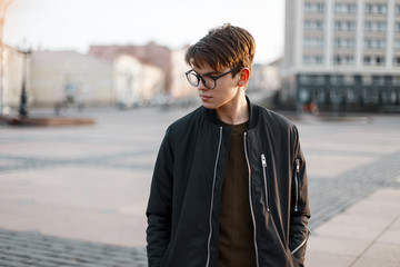 Handsome young hipster man in stylish glasses with a fashionable hairstyle in a fashionable black jacket  posing on the street on a spring day in the city. Attractive guy on vacation.
